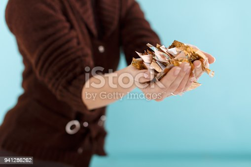 1016084100istockphoto woman hand holding golden confetti 941286262