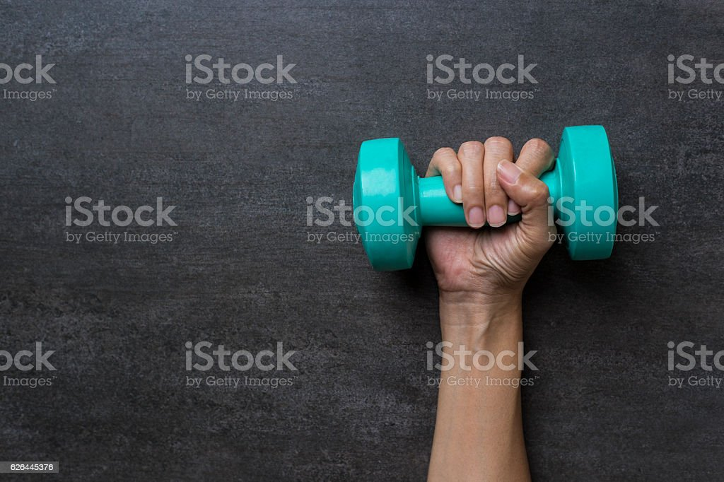 woman hand holding green dumbbell on black background stock photo