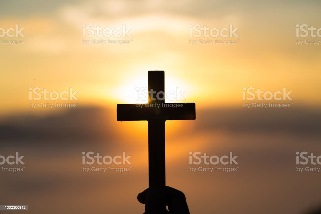 Woman hand holding holy lift of christian cross with light sunset background. stock photo