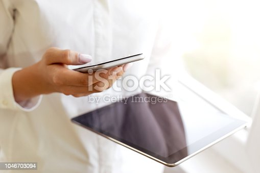 Woman hand holding mobile phone and digital tablet data synchronization