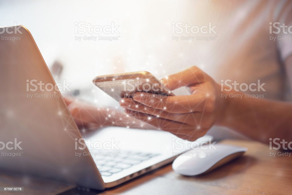 Mano de mujer con teléfono móvil y portátil de sincronización de datos - foto de stock