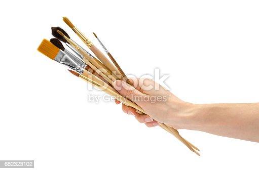 istock woman hand holding paintbrushes 682323102