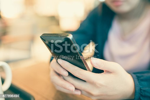 istock Woman hand holding phone 827896494