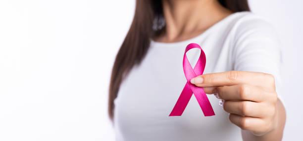 mulher segurando a fita rosa de consciência do câncer de mama. saúde conceitual e medicina. - outubro rosa - fotografias e filmes do acervo