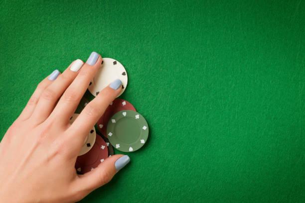 frau hand mit poker-chips auf grüne casino filz hintergrund - bester nagellack stock-fotos und bilder