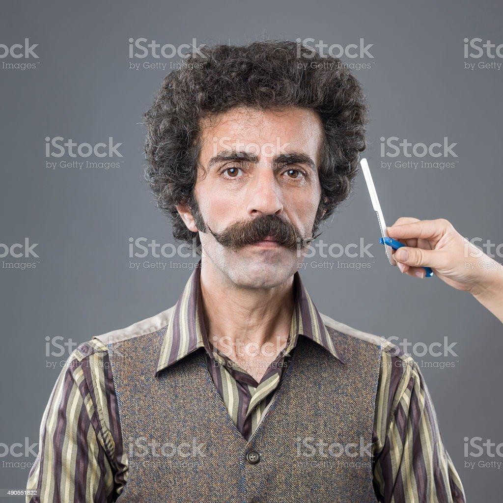 Woman Hand Holding Razor Over Man's Handlebar Mustaches stock photo