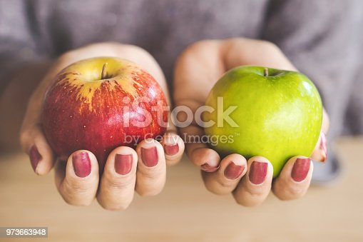 woman hand holding red and green apple fruit for diet