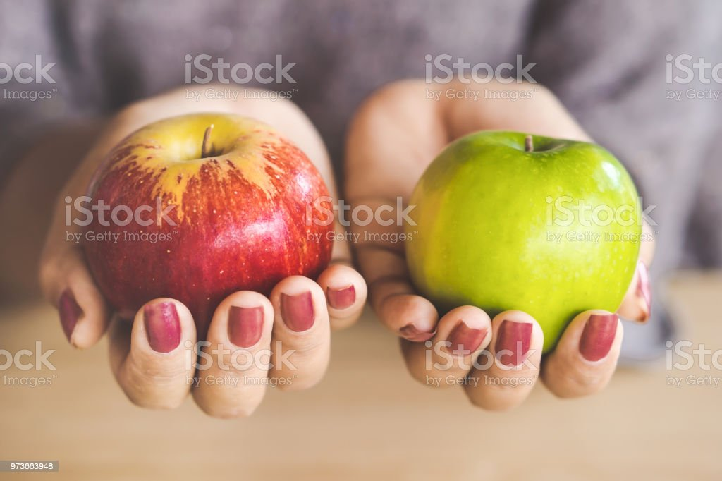 woman hand holding red and green apple fruit for dieting concept background stock photo