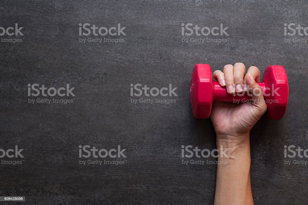 woman hand holding red dumbbell on black background – Foto
