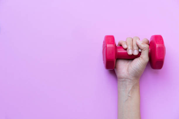 woman hand holding red dumbbell on pink background stock photo