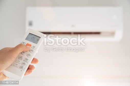 istock woman hand holding remote controller directed on the air conditioner inside the room and set at ambient temperature,25 degrees celsius. 1148724114