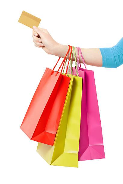 Mano de mujer sosteniendo bolsas de la compra y tarjeta de crédito - foto de stock