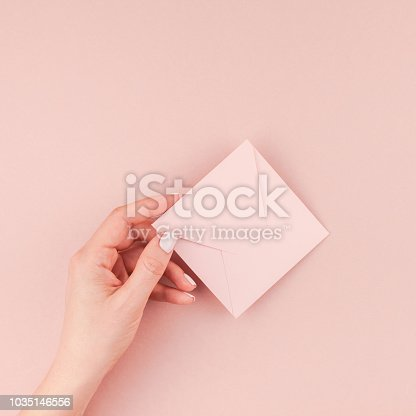 831932306 istock photo Woman hand holding small pink love letter 1035146556
