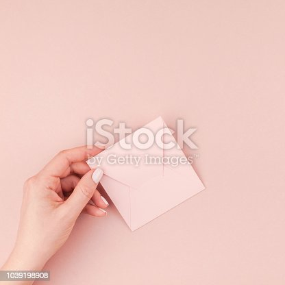 831932306 istock photo Woman hand holding small pink love letter 1039198908