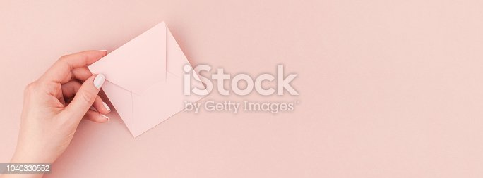Long wide banner of woman hand holding small love letter with copy space on millennial pink background in minimalism style. Concept template for feminine blog, social media