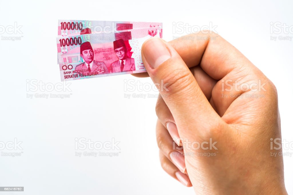 Woman hand holding small size paper banknotes of Indonesian rupiah royalty-free stock photo