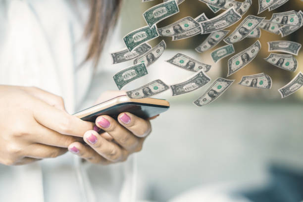 woman hand holding smart phone transfer money online woman hand holding smart phone transfer money online with paper currency flying money to burn stock pictures, royalty-free photos & images