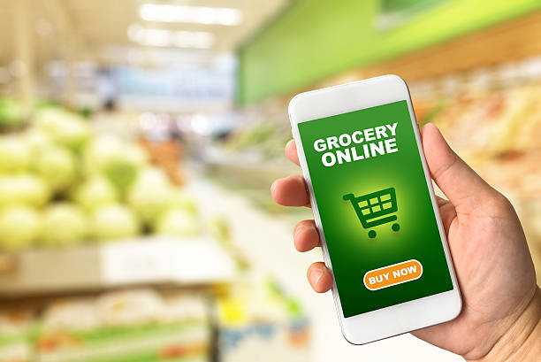 Woman hand holding smartphone against blur bokeh of store Woman hand holding smartphone against blur bokeh of store background Grocery online concept convenience stock pictures, royalty-free photos & images