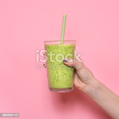 istock Woman hand holding smoothie shake against pink wall 660563142