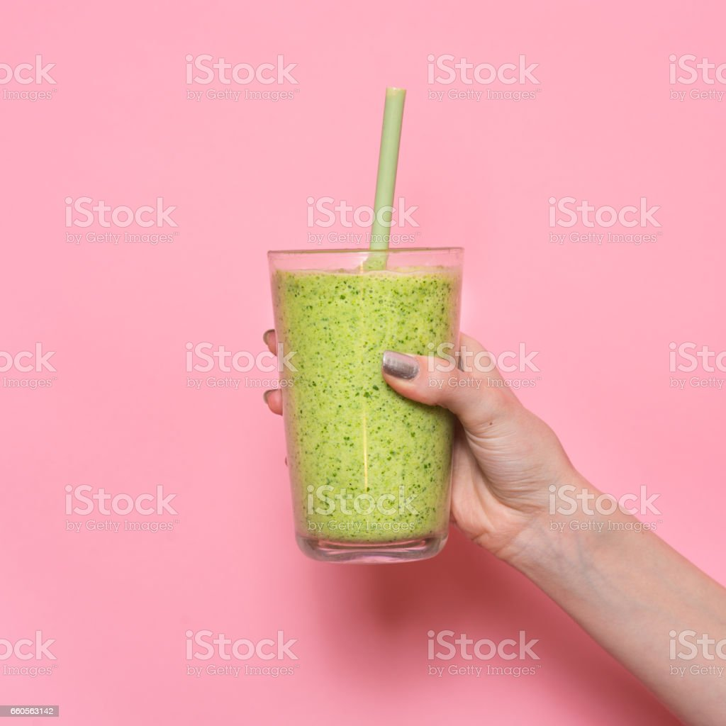 Woman hand holding smoothie shake against pink wall stock photo