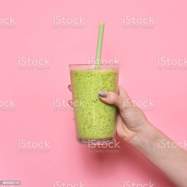 Woman hand holding smoothie shake against pink wall. Drinking green healthy smoothie concept.