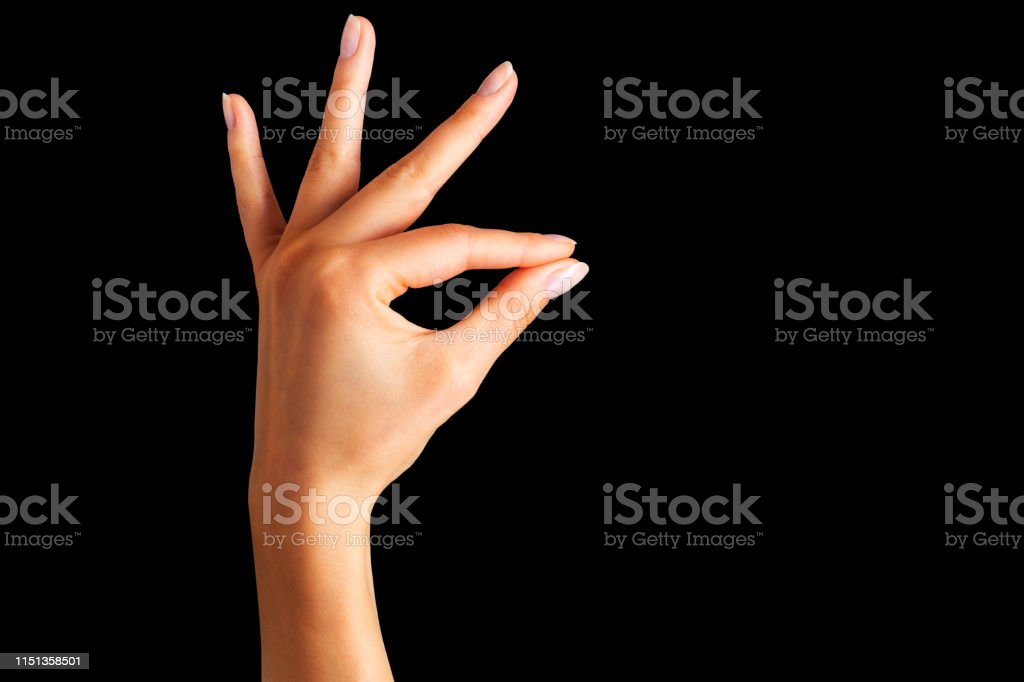 Woman hand holding something with two fingers on black background....