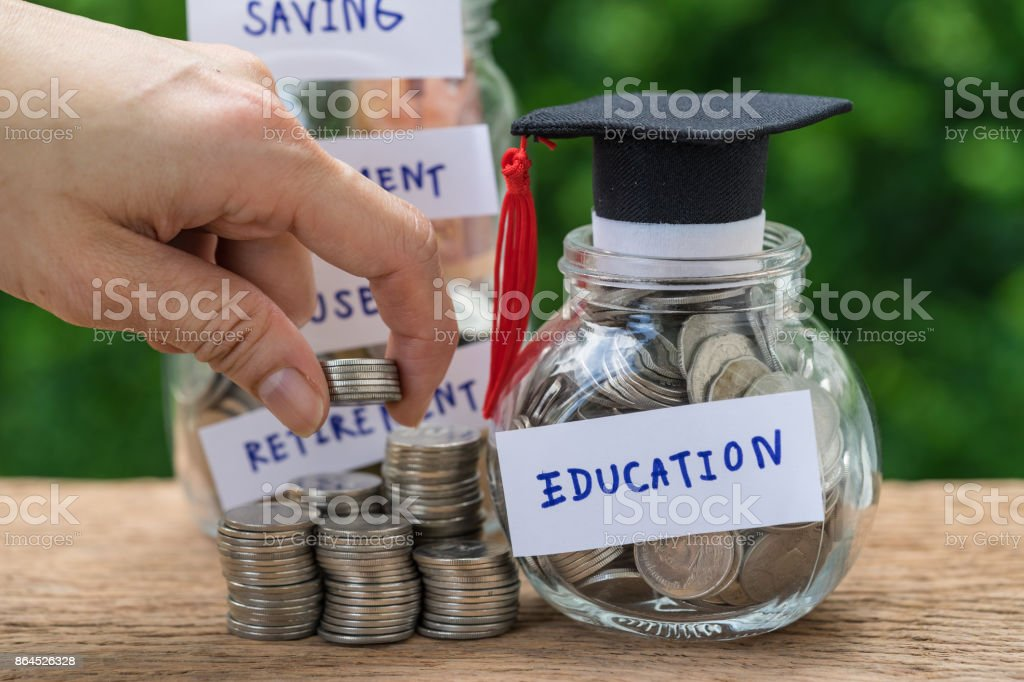 Woman hand holding stack of coins money and glass jar with full of coins and graduates hat label as Education, education or savings concept stock photo
