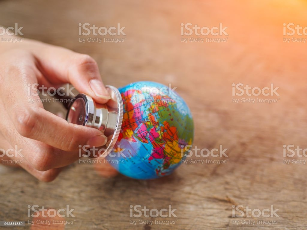 woman hand holding stethoscope with globe on wooden texture background. save earth, save environment concept. zbiór zdjęć royalty-free