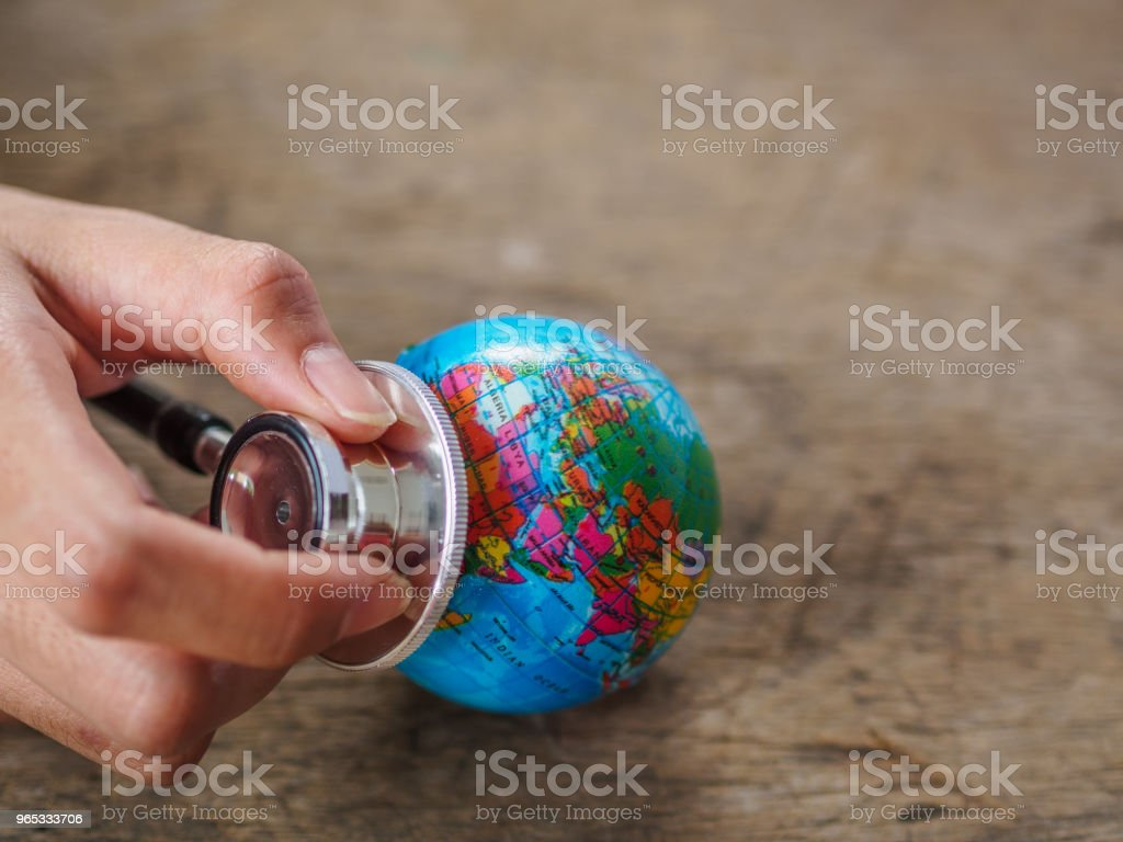 woman hand holding stethoscope with globe on wooden texture background. save earth, save environment concept. royalty-free stock photo
