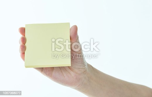 Woman hand holding sticky note on white background.
