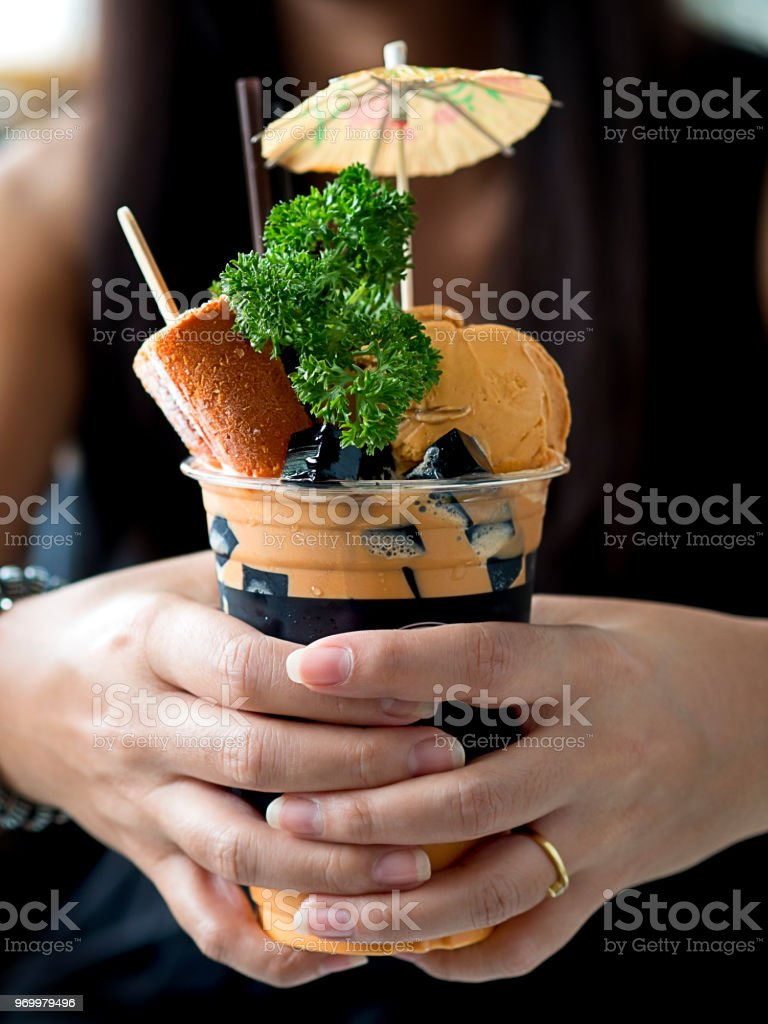 Woman hand holding Thai style milk tea or Thai tea frappe decorated with whipped cream and Thai tea ice cream and popsicle for Thai style drinking and dessert stock photo