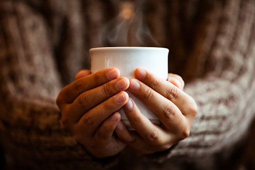 Woman hand holding the cup of coffee or tea in the cafe in rainy day