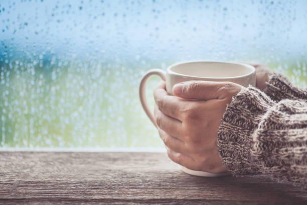 frau hand hält die tasse kaffee oder tee auf regentag fensterhintergrund - regenzeit stock-fotos und bilder