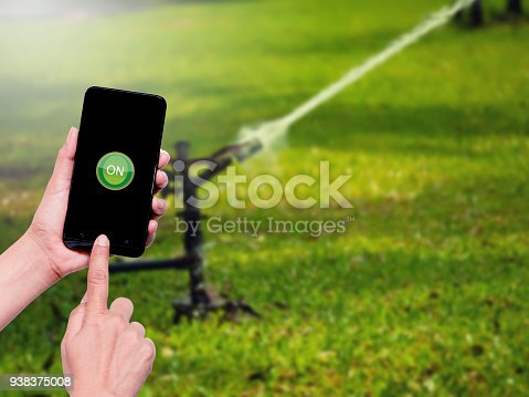 istock Woman hand holding the mobile phone with button ON  icon on screen for automatic water control system in agriculture 938375008