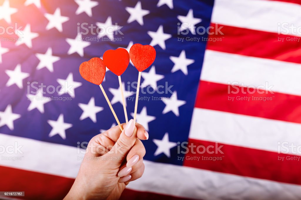 Woman hand holding three red hearts shape on stick in front of american flag. Visual concept of preparation for Independence Day. Fourth of July patriotic consept stock photo
