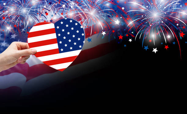 Woman hand holding USA flag in shape heart and fireworks background for 4 july independence day stock photo