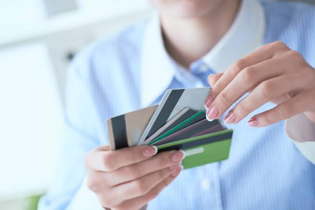 Frau Hand hält verschiedene Kreditkarten und treffen Wahl mit einer anderen Hand Nahaufnahme. – Foto