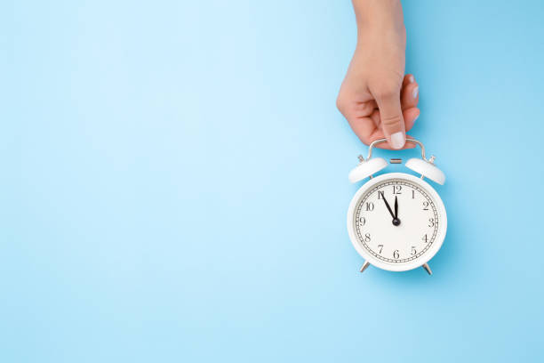 Woman hand holding white alarm clock on light blue table background. Pastel color. Time concept. Closeup. Empty place for text, quote or sayings. Top down view. stock photo