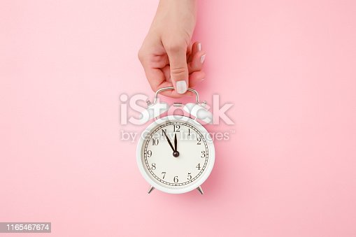 istock Woman hand holding white alarm clock on light pastel pink background. Time concept. Closeup. Top view. 1165467674