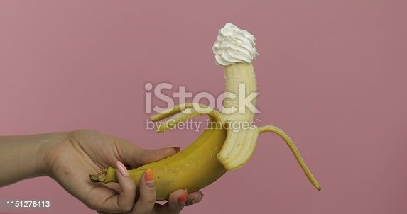 Woman hand holds banana with whipped cream on top of the fruit.  Pink background