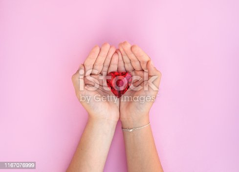 823097608istockphoto woman hand holds red heart. 1167076999