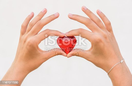 823097608istockphoto woman hand holds red heart. 1167077030