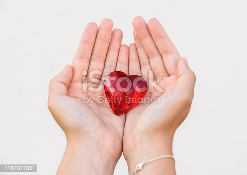 823097608istockphoto woman hand holds red heart. 1167077031