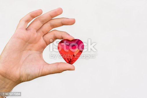 823097608istockphoto woman hand holds red heart. 1167077034