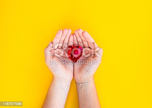 823097608istockphoto woman hand holds red heart. 1167077035