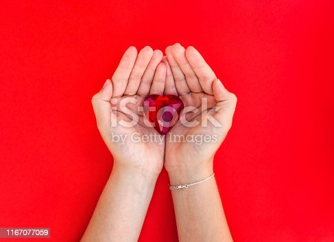 823097608istockphoto woman hand holds red heart. 1167077059