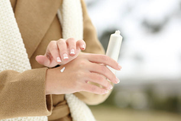 Woman hand hydrating skin applying cream in winter stock photo