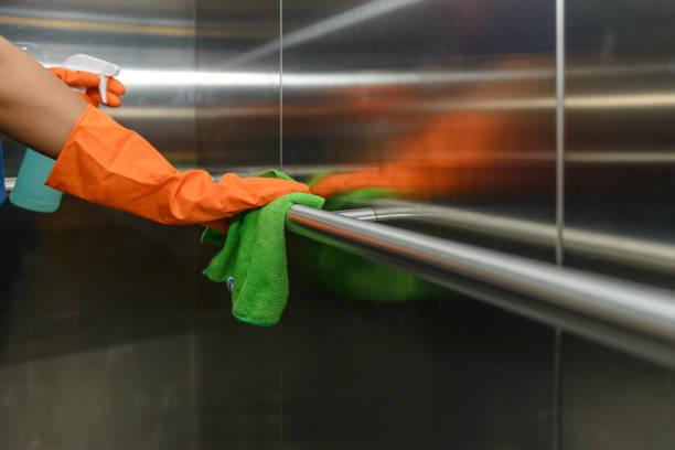 Frau Hand in schützenden orange Gummihandschuhe halten grüne Mikrofaser Reinigungstuch und Wischen Staub mit einer SprühsterilisationLösung machen Reinigung und Desinfektion für eine gute Hygiene – Foto