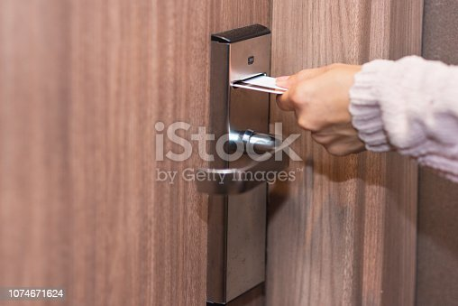 istock Woman hand inserting card to open electronic lock in hotel door 1074671624