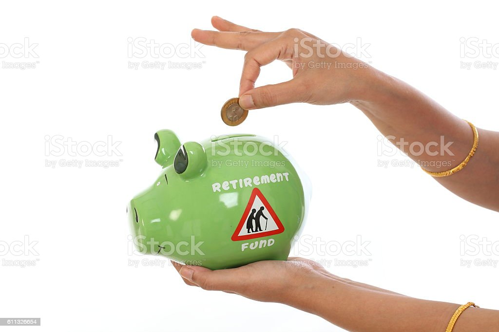 Woman hand inserting coin in a piggy bank stock photo